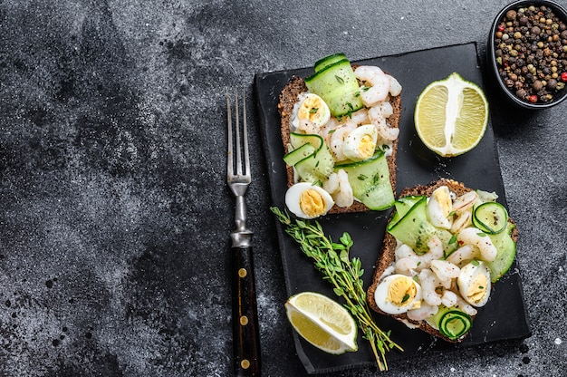Fresh toasts with shrimp, prawns, quail eggs and cucumber on rye bread. black background. top view. copy space.