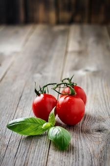 古い木の表面にバジルのフレッシュ トマト チェリー ブランチ。選択と集中。