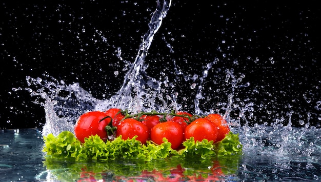 Fresh tomato cherry and green fresh salad with water drop splash. macro drops of water fall on the red cherry tomatoes and make splash