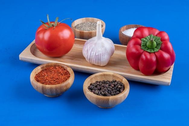 Свежие помидоры, чеснок и красный перец на деревянной тарелке.