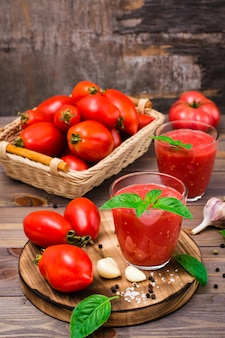 Fresh tomato juice with basil leaves in glasses and ingredients for its preparation on a wooden table