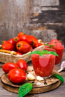 Fresh tomato juice with basil leaves in glasses and tomatoes on a wooden table