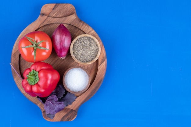 Fresh tomato, onion and red bell pepper on wooden board.