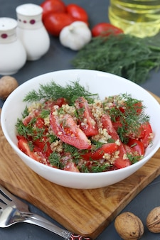 Fresh tomato salad with garlic, dill and nut dressing in a white bowl on wooden board, selective focus, healthy eating day, vertical format