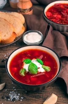 양배추와 비트 뿌리를 곁들인 신선한 토마토 수프. 갈색 배경에 사 우 어 크림과 함께 보르시.