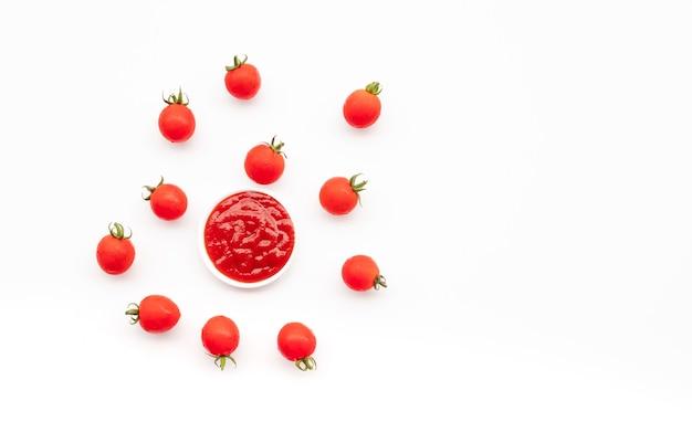 白い背景の上の小さな皿にトマトソースとフレッシュトマト。有機食品と野菜の概念のアイデア。上面図