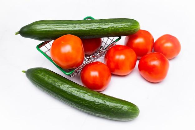 スーパーマーケットの金属製バスケットに入ったフレッシュトマトとキュウリ。