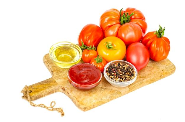 Свежие помидоры и кетчуп в стеклянной форме.