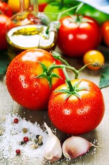 Свежие помидоры и оливковое масло на деревянном столе