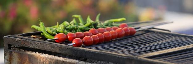 Свежие помидоры и перец на шпажках на гриле крупным планом