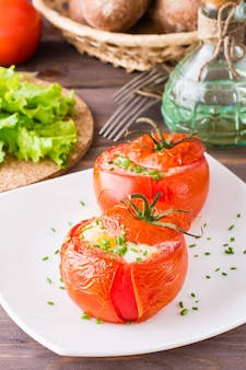 Fresh tomatoes baked with cheese and egg sprinkled with green onions on a plate on a wooden table