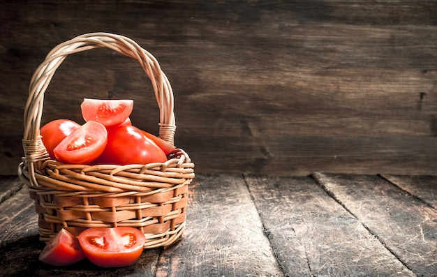 Fresh tomatoes in a basket. on a wooden background.