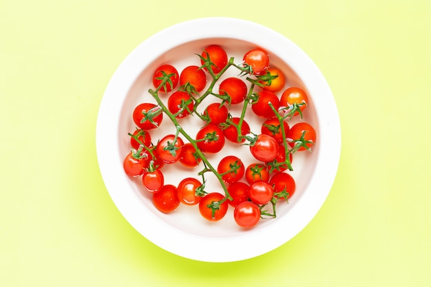 Fresh tomatoes in a bowl of water on green.
