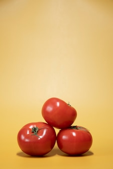 Fresh tomatoes on a bright yellow background in an advertising food photo style. vertical frame