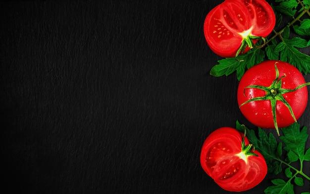Свежие помидоры разрезать пополам на черной каменной поверхности