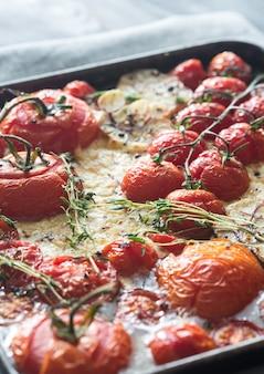 トレイにフレッシュトマト、フェタチーズ、ニンニク、タイム