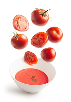 Fresh tomatoes flying and homemade tomato cream in a bowl