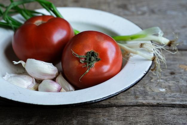 新鮮なトマト、ニンニク、ねぎ、古い木製のテーブル。