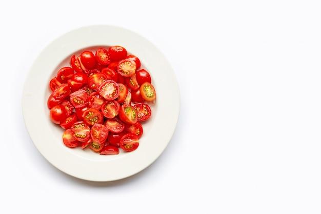 Fresh tomatoes, half cut on white dish.