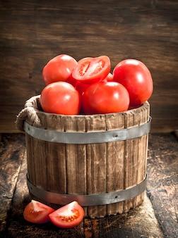 木製の背景に木製のバケツで新鮮なトマト