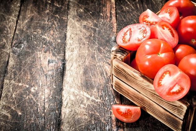 古い箱に入ったフレッシュトマト。木製の背景に。