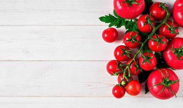 Свежие помидоры на ветке с листьями в правом верхнем углу на белой деревенской деревянной поверхности