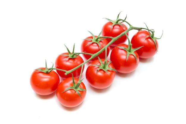 白で隔離される茎の新鮮なトマト。