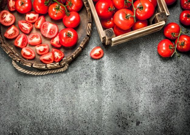 Свежие помидоры на подносе на деревенском фоне