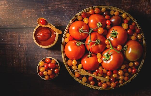 木製のテーブルの上の新鮮なトマトトマトの塩を処理するために農家によって収穫されました。