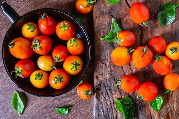 Fresh tomatoes in a pan on a wooden background.