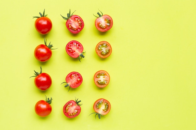 Fresh tomatoes, whole and half cut isolated on green.