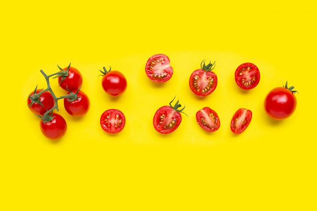 Fresh tomatoes, whole and half cut isolated on yellow.