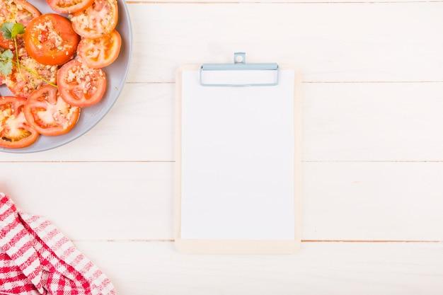 Свежие помидоры с буфером обмена на кухонном столе