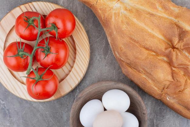Свежие помидоры с яйцами и хлебом на мраморном фоне. фото высокого качества