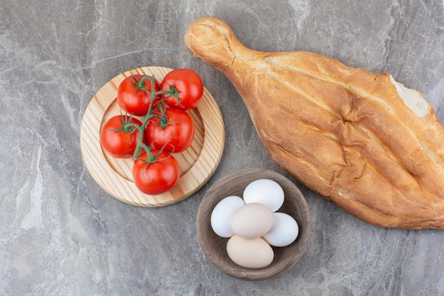 Fresh tomatoes with eggs and bread on marble background. high quality photo