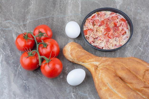 Свежие помидоры с яичницей и хлебом на мраморном фоне. фото высокого качества