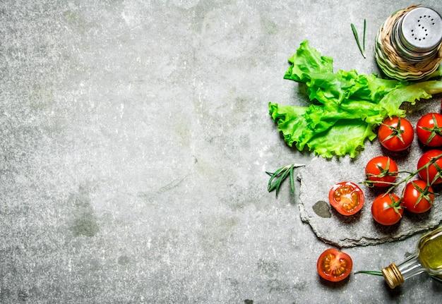 レタスとオリーブオイルのフレッシュトマト。石の背景に。