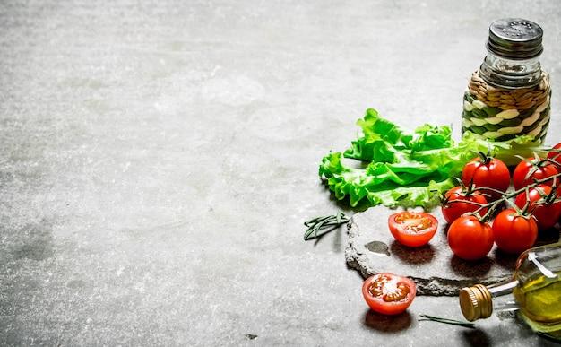 Свежие помидоры с листьями салата и оливковым маслом. на каменном фоне.