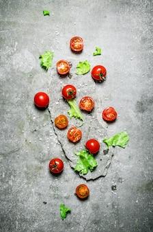 石のスタンドにレタスとフレッシュトマト。石の背景に。