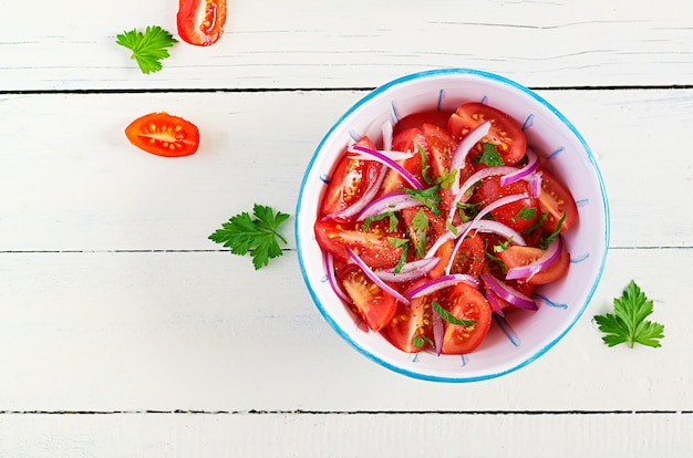 Fresh tomatoes with red onion and spices in a blue bowl.  concept healthy appetizer. white wooden background. top view, copy space