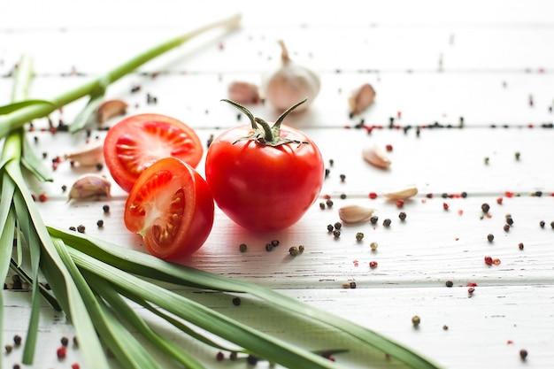 Свежие помидоры со специями. органическая здоровая еда на деревянной предпосылке. зеленый чеснок летние и осенние овощи.