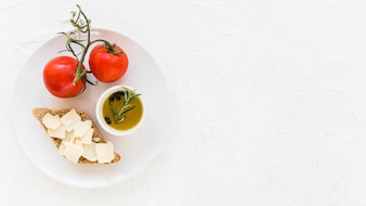 Fresh tomatoes with virgin healthy olive oil and bread on white background