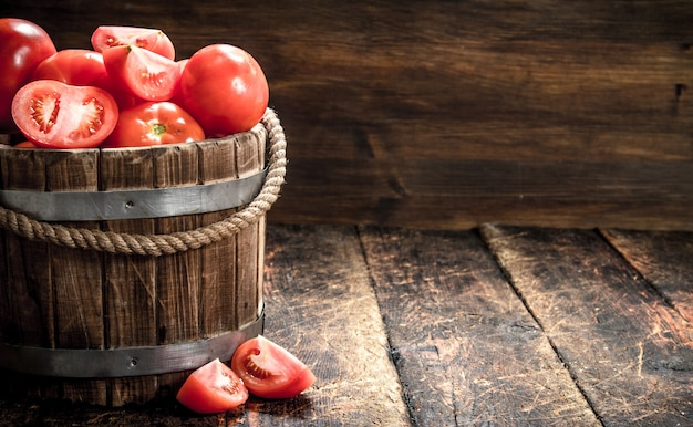 Fresh tomatoes in a wooden bucket. on a wooden background.