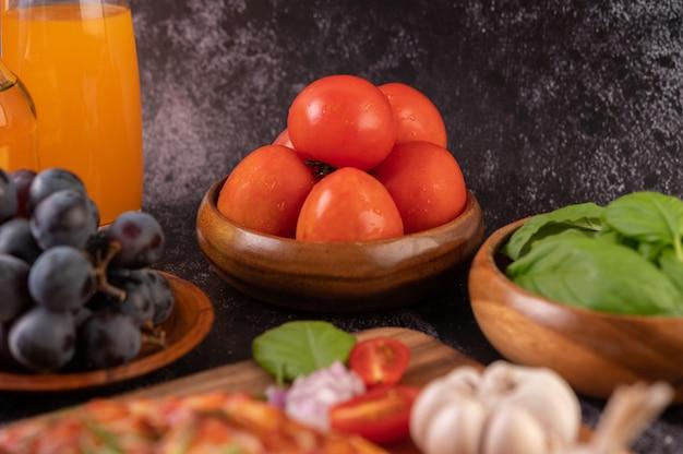 Pomodori freschi in una tazza di legno, uva e succo d'arancia in un bicchiere.
