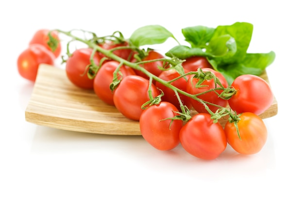Fresh tomatoes on wooden plate