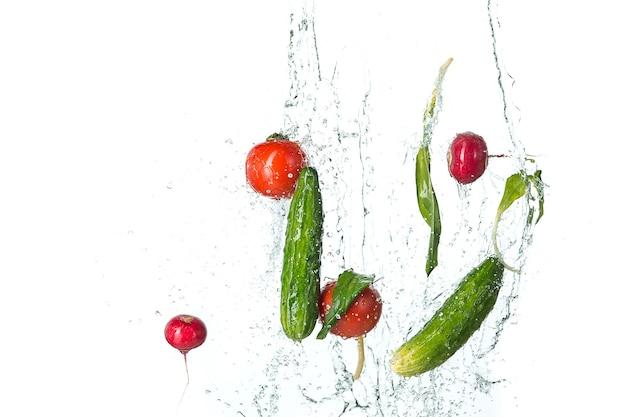 The fresh tomatos, cucumbers, radish in spray of water on white.