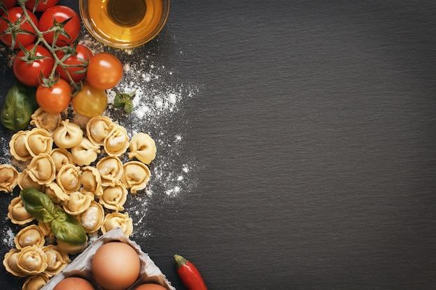 Свежая паста тортеллини и ингредиенты на темной доске, вид сверху