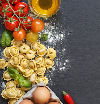 Fresh tortellini pasta and ingredients on a dark board with copy space