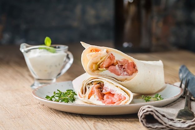 Fresh tortilla wrap with vegetables and salmon on plate