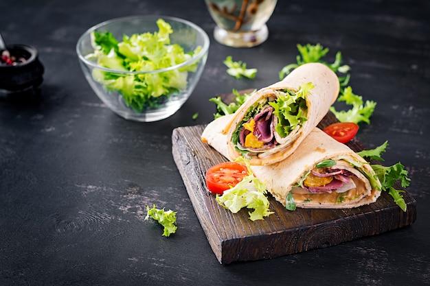 新鮮なトルティーヤは、木の板にハムビーフと新鮮な野菜で包みます。ビーフブリトー。メキシコ料理。コピースペース
